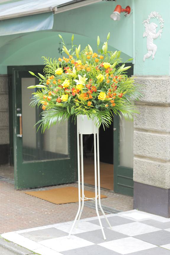 <p>温かみ溢れる黄色とオレンジを中心とした暖色系2色仕立てのスタンド花です。</p>