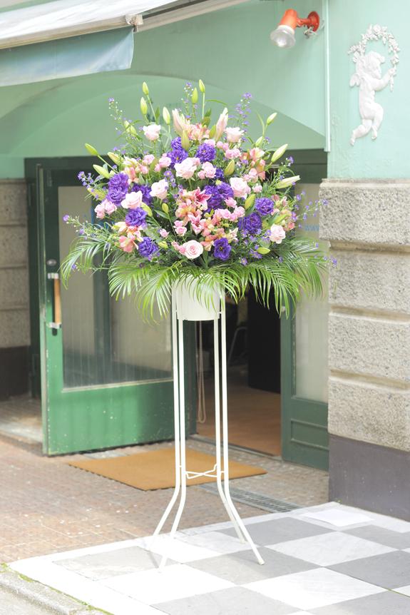 <p>華やかな装飾に重厚感を加えたピンクとパープル系2色仕立てのスタンド花です。</p>